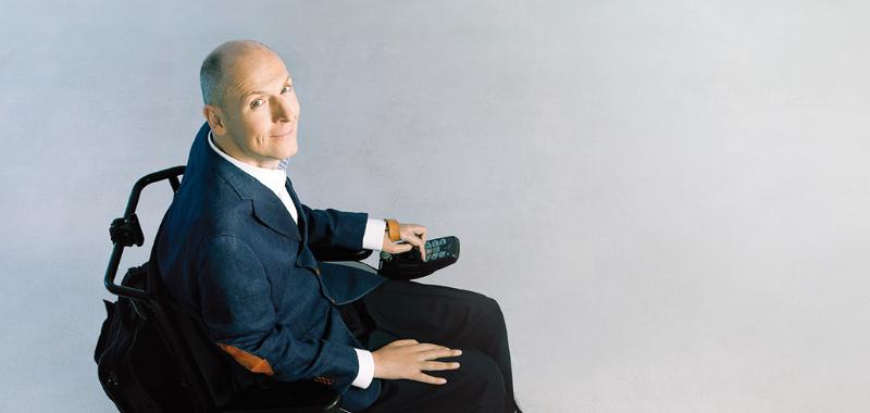 Portret uśmiechniętego Piotra Pawłowskiego siedzącego na wózku