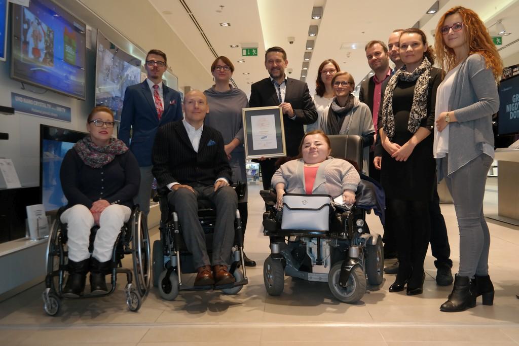 Piotr Pawłowski na wspólnym zdjęciu z ok. tuzinem osób. Jeden z mężczyzn prezentuje certyfikat dostępności