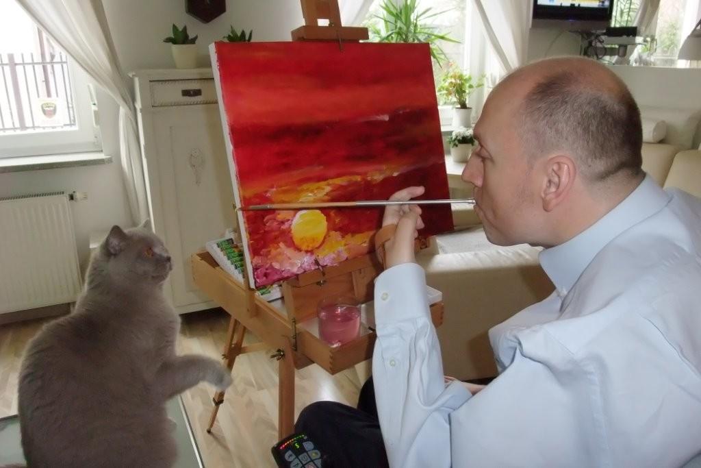 Piotr Pawłowski maluje obraz trzymając pędzel w ustach w towarzystwie obserwującego go kota