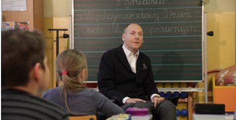 Piotr Pawłowski rozmawia z dziećmi na tle tablicy w szkolnej klasie