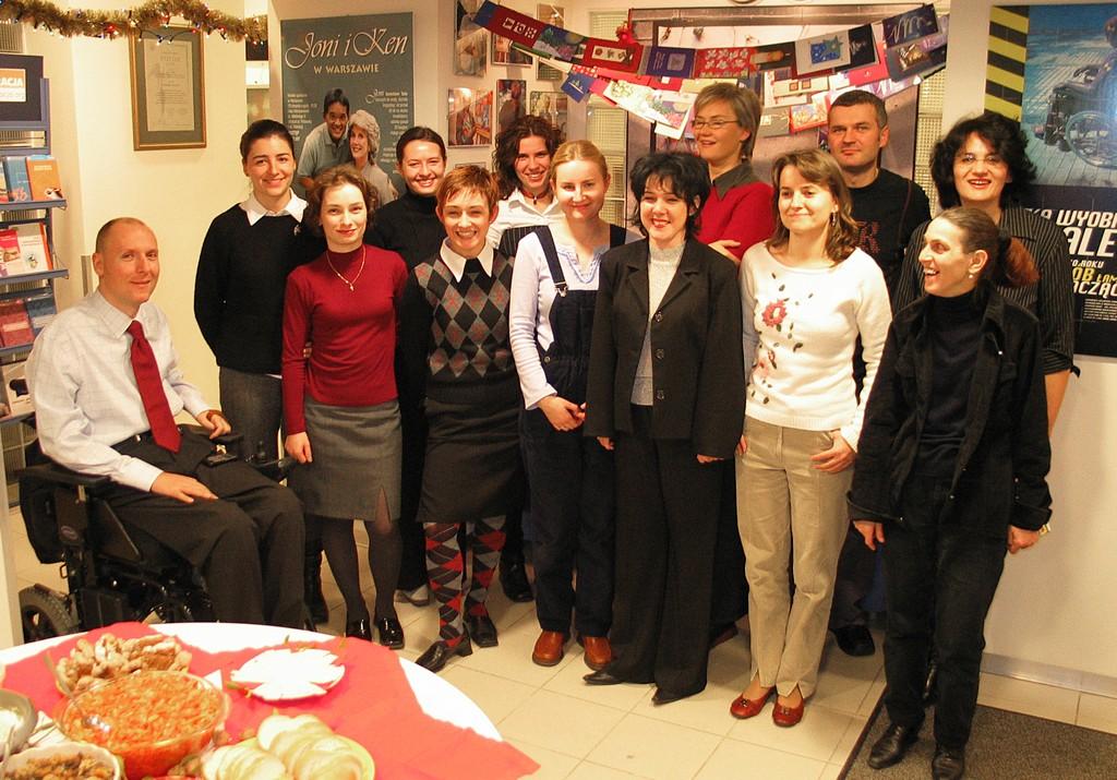 Piotr Pawłowski pozuje do wspólnego zdjęcia z kilkunastoma pracownikami Integracji w biurze stowarzyszenia